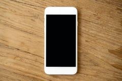 Modellbild av den vita mobiltelefonen med mellanrumssvartskärmen på tappningträtabellen arkivfoton