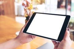 Modellbild av händer för kvinna` som s rymmer svart minnestavlaPC med den tomma vita skrivbords- skärm-, bärbar dator- och kaffek Arkivfoton