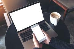 Modellbild av händer som rymmer den tomma mobiltelefonen, medan genom att använda bärbara datorn med den tomma vita skrivbords- s Royaltyfria Foton