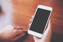 Modellbild av händer som rymmer den vita mobiltelefonen med mellanrumssvartskärmen med den varma kaffekoppen royaltyfria bilder