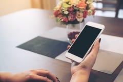 Modellbild av händer som rymmer den vita smartphonen med skärmen och bärbara datorn för mellanrumssvart den skrivbords- royaltyfri foto