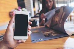 Modellbild av mobiltelefon för hand för man` s en hållande vit med mellanrumssvartskärmen i modern läs- tidning för kafé och för  Arkivbilder