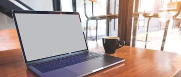 Modellbild des Laptops mit leerem Bildschirm auf Holztisch nahe durch Fenster Lizenzfreie Stockfotos