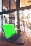 Modellbild des Laptops mit leerem grünem Schirm und Kaffeetasse auf Holztisch Lizenzfreie Stockbilder