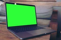 Modellbild des Laptops mit leerem grünem Tischplattenschirm auf Holztisch Stockfotografie