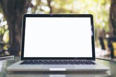 Modellbild des Laptops mit leerem weißem Schirm auf Glastisch an im Freien mit grüner Natur Lizenzfreie Stockfotografie