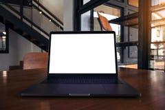 Modellbild des Laptops mit leerem weißem Schirm auf Holztisch nahe durch Fenster Lizenzfreies Stockbild