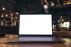 Modellbild des Laptops mit leerem weißem Schirm auf Holztisch nahe durch Fenster Lizenzfreie Stockfotos