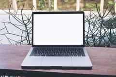 Modellbild des Laptops mit leerem weißem Schirm auf Weinleseholztisch Lizenzfreie Stockbilder