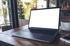 Modellbild des Laptops mit leerem weißem Schirm, Smartphone und Kaffeetasse auf Holztisch nahe durch Fenster Stockfotografie