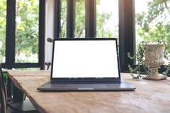 Modellbild des Laptops mit leerem weißem Tischplattenschirm auf Weinleseholztisch Stockbilder