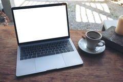 Modellbild des Laptops mit leerem weißem Tischplattenschirm und Kaffeetasse, Buch, Kerze auf Holztisch Stockfoto