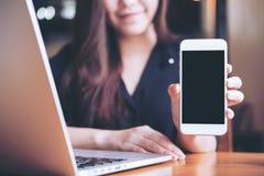 Modellbild einer asiatischen Schönheit des smiley, die weißen Handy mit leerem schwarzem Schirm bei der Anwendung des Laptops häl Lizenzfreie Stockfotos