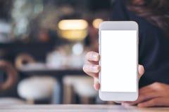 Modellbild einer Frau, die auf dem Tisch weißen Handy mit leerem Bildschirm hält und zeigt lizenzfreie stockfotografie