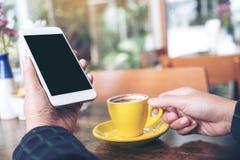 Modellbild einer Hand, die weißen Handy mit leerem schwarzem Tischplattenschirm und gelber Kaffeetasse auf Holztisch hält Lizenzfreies Stockbild
