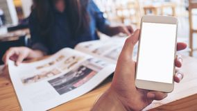 Modellbild einer Mann ` s Hand, die weißen Handy mit leerem Bildschirm in der modernen Café- und Unschärfefrauenlesezeitung hält stockbilder