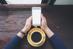 Modellbild eines Frau ` s übergibt das Halten des weißen Handys mit leerem Bildschirm mit gelben heißen Kaffeetassen auf Weinlese Stockbild