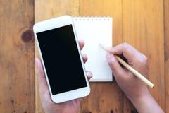 Modellbild för bästa sikt av en hållande vit mobiltelefon för hand med mellanrumssvartskärmen och handstil på en tom vit anteckni Royaltyfri Fotografi