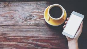 Modellbild von den Händen, die weißen Handy mit leerem Bildschirm mit gelben heißen Kaffeetassen auf Weinleseholztisch halten Lizenzfreies Stockfoto