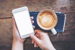 Modellbild von den Händen, die weißen Handy mit leerem Bildschirm mit Kaffeetassen auf Weinleseholztisch halten Lizenzfreie Stockfotos
