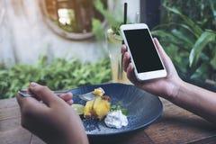 Modellbild von den Händen, die weißen Handy mit leerem schwarzem Schirm beim Essen des gelben Zitronenklumpenkuchens auf Holztisc stockfoto