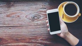 Modellbild von den Händen, die weißen Handy mit leerem schwarzem Schirm mit gelben heißen Kaffeetassen auf Weinleseholztisch halt Stockfotos