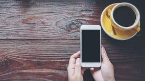 Modellbild von den Händen, die weißen Handy mit leerem schwarzem Schirm mit gelben heißen Kaffeetassen auf Weinleseholztisch halt Lizenzfreie Stockfotos