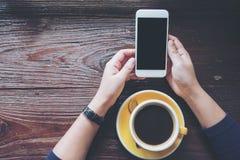 Modellbild von den Händen, die weißen Handy mit leerem schwarzem Schirm mit gelben heißen Kaffeetassen auf Weinleseholztisch halt Stockbilder