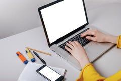 Modellbildmobiltelefon, datorhand som skriver med den tomma skärmen för text, flicka som använder bärbara datorn och söker inform arkivfoton