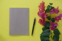 Modellbraunnotizbuch mit Raum für Text auf gelbem Hintergrund und Blumen lizenzfreie stockbilder