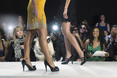 Modelle in den hohen Absätzen gegen Zuschauer stockfotos