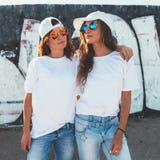 Modelle, die einfaches T-Shirt und die Sonnenbrille aufwirft über Straße wa tragen stockfotos