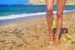 Modellen annonserar bohemiska grekiska sandaler på stranden royaltyfria foton