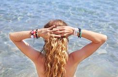 Modellen annonserar grekiska smycken på stranden royaltyfria foton