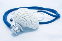 Modellen av den mänskliga hjärnan med invecklade saker och den blåa stetoskopet är på vit enhetlig bakgrund Patologiskt begreppsf fotografering för bildbyråer