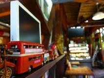 Modellen av en retro röd london buss dekorerar på trätabellen arkivfoton