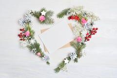 Modellen av julkransen i form av hjärta med arket av papper dekorerade med vita snöflingor och kottar Trävit arkivbilder