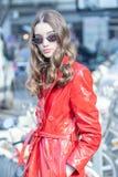 Modellen bär en skinande röd regnrock royaltyfria foton