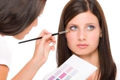 Modellen för mode för sminkkonstnärkvinnan applicerar ögonskugga royaltyfri bild