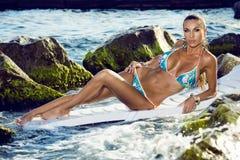 Modellen i bikini solbadar på havet Royaltyfri Foto