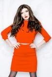 Modellen med långt hår som bär den röda klänningen med vågor, krullar frisyren Royaltyfria Foton