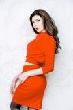 Modellen med långt hår som bär den röda klänningen med vågor, krullar frisyren Royaltyfri Foto