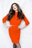 Modellen med långt hår som bär den röda klänningen med vågor, krullar frisyren Fotografering för Bildbyråer