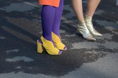 Modeller bär ett par av gula skor med häl och purpurfärgade guld- ankelkängor för sockor och arkivfoto