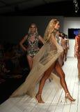 Modeller går landningsbanan i märkes- baddräkt under den Furne Amato modeshowen Arkivfoto