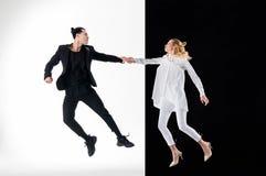 Modeller i svartvita kläder som hoppar för trevligt skott royaltyfri bild