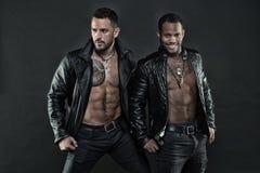 Modeller som bär läderomslag på kala torso, modebegrepp Cyklister med sex packe och tatuerade bröstkorgar Afrikansk man arkivbilder