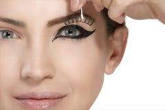 Modellera att applicera konstgjord ögonfransförlängning på rökigt öga Fotografering för Bildbyråer