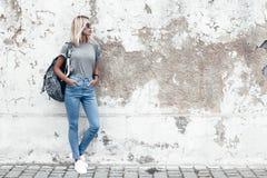 Modellera att posera i vanlig tshirt mot gataväggen arkivbilder