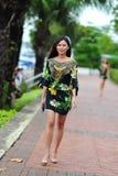 Modellera att ställa ut vibrerande och lyxiga designer av Camilla (med Wattletree) under händelse för mode för Singapore yachtshow Arkivfoton